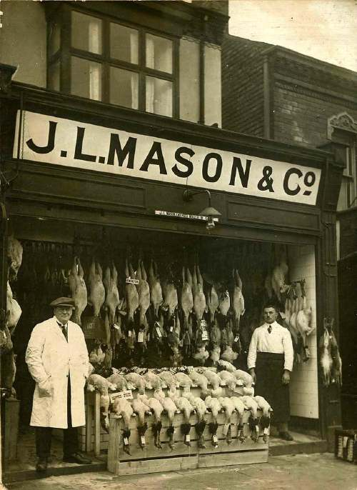 "This picture was supplied by Mary Gibbons who moved to 1885 Pershore Road in 1947 when her father bought the shop from his employer, Arthur Turner.  He decided to keep the name of JL Mason so that the customers would still recognise the shop. JL Mason was primarily a fishmongers but a small sign above the entrance says that it was also a, ""licensed dealer in game"". Mary thinks the picture was of Christmas stock as she remembers it looking like this at Christmas when she was a child. Normally there would just have been a display of fish on the marble slab. Note the sawdust on the floor to prevent slipping. Mary's father, Jim Bird, is the chap on the right and at this time he was a fishmonger's assistant.  Less than ten years later he would own the shop! Thanks to Mary and the DJ Norton website for this photo."