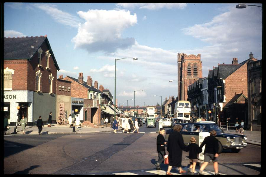 Looking north towards the city from the Pershore Road / Watford Road roundabout. On the corner of Watford Road is George Mason's shop. St Agnes Church is still present - it's now a supermarket. The newly-build Lloyds Bank building is present in the row of Victorian shops on the right.